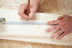 Mãos que medem a prancha de madeira com fita e o lápis de medição Imagem de Stock