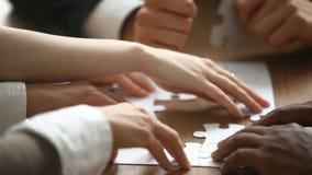 Mãos que montam o enigma de serra de vaivém, apoio no conceito dos trabalhos de equipa, close up da ajuda video estoque