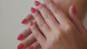 Mãos que mostram o tratamento de mãos vermelho fresco no salão de beleza do prego video estoque