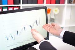 Mãos que mostram uma tela com gráfico dos dados de bolsa de valores Imagens de Stock Royalty Free