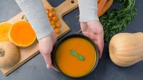 Mãos que põem a bacia de sopa do creme da abóbora sobre a tabela filme