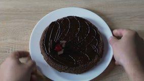 Mãos que põem o bolo de chocolate com a cereja sobre a parte superior na tabela de madeira, aniversário video estoque