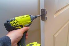 Mãos que parafusam a dobradiça na porta de madeira com chave de fenda fotos de stock royalty free