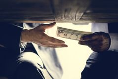 Mãos que passam o dinheiro sob a corrupção da corrupção da tabela foto de stock