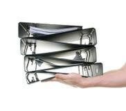 Mãos que passam uma pilha de pastas de anel Imagem de Stock Royalty Free