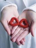 Mãos que prendem corações foto de stock royalty free