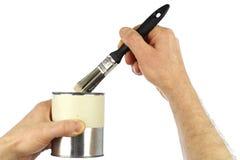 Mãos que prendem a lata do pincel e da pintura Imagem de Stock Royalty Free