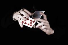Mãos que prendem muitos cartões do jogo fotografia de stock