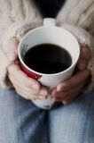 Mãos que prendem o copo do café escuro Imagem de Stock