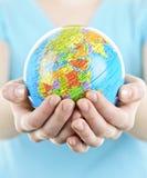 Mãos que prendem o globo imagem de stock royalty free
