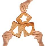 Mãos que prendem o pão com símbolos do Natal foto de stock