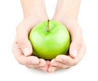 Mãos que prendem para fora uma maçã Fotografia de Stock