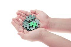 Mãos que prendem partes de enigma de serra de vaivém Imagem de Stock Royalty Free