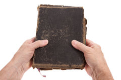 Mãos que prendem uma Bíblia Imagens de Stock