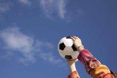 Mãos que prendem uma esfera de futebol Imagem de Stock Royalty Free