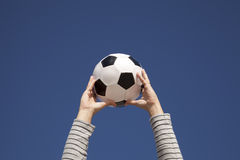 Mãos que prendem uma esfera de futebol Imagem de Stock
