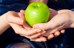 Mãos que prendem uma maçã Fotos de Stock Royalty Free