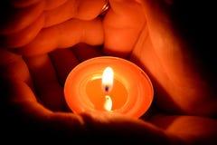 Mãos que prendem uma vela Imagem de Stock