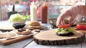 Mãos que preparam o cheeseburger video estoque