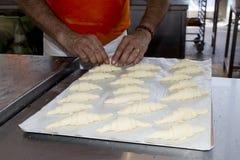 Mãos que preparam o croissant francês Imagens de Stock