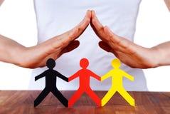 Mãos que protegem povos chain de papel coloridos Fotos de Stock