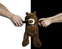 Mãos que puxam um urso de peluche imagem de stock royalty free