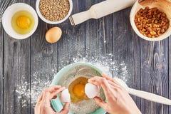 Mãos que quebram um ovo para flour para o pão, a pizza ou a torta da receita fazendo os ingridients, configuração lisa do aliment Fotos de Stock