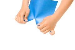 Mãos que rasgam o papel azul ilustração stock