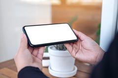 Mãos que realizam e que usam um telefone celular preto com tela vazia horizontalmente para olhar no ar livre fotografia de stock royalty free