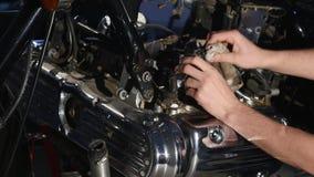 Mãos que reparam a motocicleta Close up do tiro filme