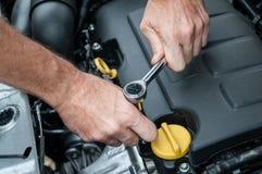 Mãos que reparam um motor de automóveis com uma chave Imagens de Stock Royalty Free