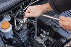 Mãos que reparam um motor de automóveis com uma chave Fotografia de Stock Royalty Free