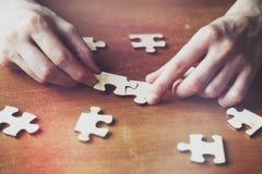 Mãos que resolvem o enigma de serra de vaivém Imagens de Stock Royalty Free