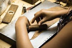 Mãos que rolam charutos em uma fábrica Fotos de Stock