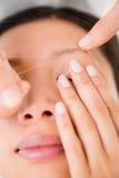 Mãos que rosqueiam a sobrancelha da mulher bonita Foto de Stock Royalty Free