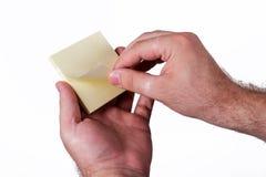 Mãos que sustentam notas amarelas Imagens de Stock Royalty Free