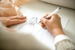 Mãos que tiram um esboço do projeto da roupa fotos de stock royalty free