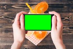 Mãos que tomam a foto das laranjas Tela verde Conceito da tecnologia Foto de Stock