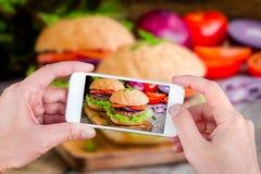 Mãos que tomam hamburgueres da foto com smartphone Imagem de Stock