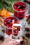 Mãos que tomam o vinho ferventado com especiarias foto com smartphone Fotografia de Stock