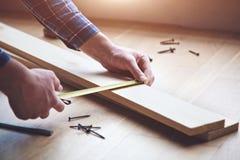 mãos que trabalham com a fita de medição de madeira Imagem de Stock