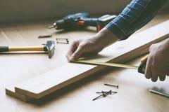 mãos que trabalham com a fita de medição de madeira Fotos de Stock