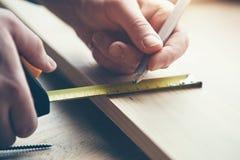 mãos que trabalham com a fita e o lápis de medição de madeira Fotos de Stock