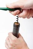 Mãos que uncorking um frasco do vinho Imagem de Stock