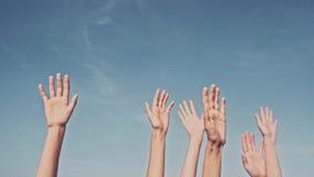 Mãos rasing dos povos no fundo do céu azul Votação, democracia ou conceito do oferecimento fotografia de stock royalty free