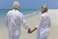 Mãos sênior felizes da terra arrendada dos pares em uma praia Foto de Stock