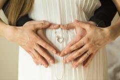 Mãos sob a forma de um coração na barriga Pares grávidos Wom Imagem de Stock