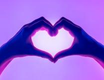 Mãos sob a forma do fundo do vermelho do coração Símbolo do coração com mão Cartão do dia dos Valentim O ` s da mulher entrega a  Foto de Stock