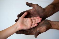 Mãos sujas pretas do homem que guardam a mão limpa da criança Fotos de Stock Royalty Free
