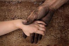 Mãos sujas pretas do homem que guardam a mão limpa da criança Imagens de Stock Royalty Free